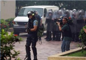 A news camera man films SWAT police as they persue students through the University of Puerto Rico in Rio Piedras. One officer stands ready with a bean bag guns.