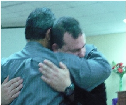 González receiving a farewell hug from some of his congregation members.  Jonathan Cintrón suggested that it would be best to give the pastor a warm sendoff before being deployed.
