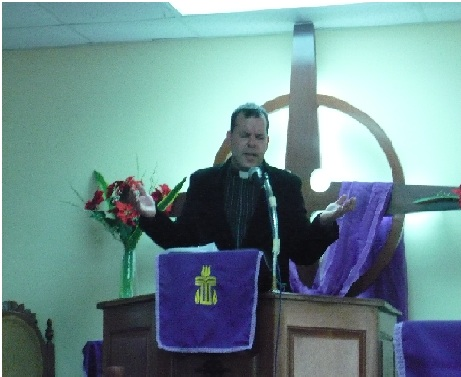 Reverend González saying a prayer at the podium of his church.  He has been serving this community for about four years.