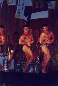 Luis (middle) in a bodybuilding competition. He won first place in his category.