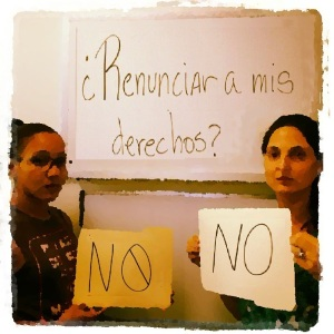 "Retreived from facebook. ""Give up my rights?"" is written in Spanish on the white board. You see her on the right, accompanied by a friend (left), both holding a sign that exclaims: No, referring to not giving up their rights as human beings."