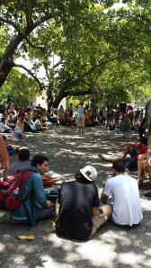 "In this picture, we can see an event that is being held at ""La Plazita"" called ""Arte en La Plazita"". Here, students gather to listen to different people recite poetry, sing, and play music, among other things. The people that frequent this event are students, usually from the departments of the Chardón building."