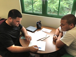 "An English Writing Center tutor helps a University of Puerto Rico-Mayagüez student polish a paper for an English course. The English Writing Center, located in Celis 323, offers writing support for students working on curricular and extracurricular English projects. ""I began coordinating the EWC in January 2013; it has been a gratifying experience to work with such a talented group of undergraduate and graduate tutors."""