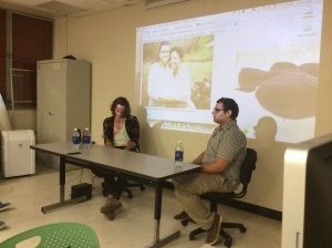Panelists Ricardo Ferrer and Gustavo Vázquez. Yolanda Arroyo is on the phone and her photograph is projected in the background