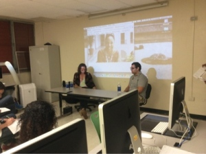 Yolanda Arroyo Pizarro answers a question via telephone while a picture of her is shown in the background. Panelists Gustavo Vazquez (left) and Ricardo Ferrer (right) are seated at  the table.