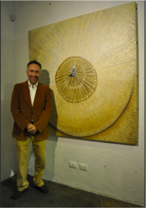 Baruch Vergara next to one of his work.