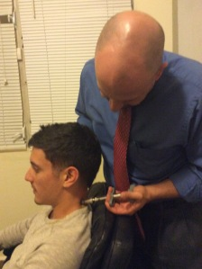 """Dr. Ismael E. Dávila adjusts a patient's neck using an activator, a mechanical chiropractic device used to manipulate the spine. Visiting a chiropractic clinic regularly helps the body restore its natural posture, taking away stress, tension and pain. """"The power that shapes the body, helps heal the body,"""" Dr. Dávila points out."""