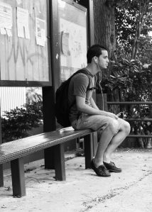 "Jose Enrique Ramirez, 23, sitting in one of the many bus stops. Being eco-friendly is on of his personal traits. ""Being in a modern world you would think that people have replaced the way they advertise around school grounds. I wish I could walk around everywhere without having to see those annoying papers"""