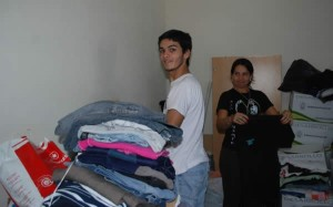 Victoria's Friend Evelyn Alvarez with her son Alexis Rivera classifying clothe.