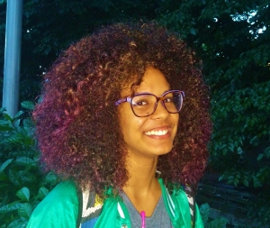 "Jeyra Rivera, 18, photographed in front of The Student Center wearing her slightly purple big curly mane. Jeyra has been wearing her natural curls for approximately 5 years now and when interviewed, she confessed that the thing she loves most about her hair is that in case she ever needs to take a nap, she literally doesn't need a pillow to do it. ""The funniest question anyone has ever asked me about my hair came from a 6 year old and he asked me if I had stick my tongue in an electricity plug."""