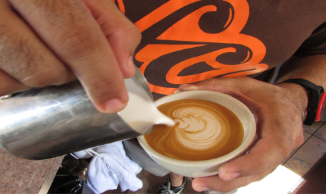 Hernán pouring cream into the coffee cup. The way he was making coffee was precisely in an Italian manner. The technique came from Italy therefore all methods and words are Italian, such as latte, barista, cappuccino, etc.