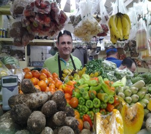 "Alsenio Pérez, 50, is at station #19 in the marketplace of Mayagüez. Over the past 31 years, he has sold vegetables and fruits. ""Fruits and vegetables come from the Earth that's why they are healthy. Everything natural is the best."""