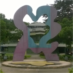 "The sculpture ""Serpentinata Caribeña"" by the French Guy Rougemont, is 19.8 feet high and made by steel painted in purple, blue and yellow colors. The Mayagüez Campus acquired the piece during the celebration of the Third International Sculpture Symposium held in 2004 in the Office of the President of the University of Puerto Rico. As part of that event, 11 national and international artists were invited to prepare sculptures that eventually acquired each of the units of the UPR system."